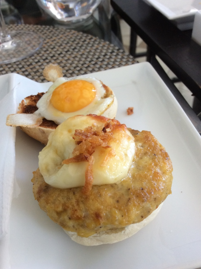 Mini chicken burger with Mediterranean dressing, quail egg and mustard sauce with pineapple and coconut.
