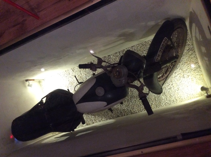 The old Ossa motorcycle was already in situ - under a glass floor!